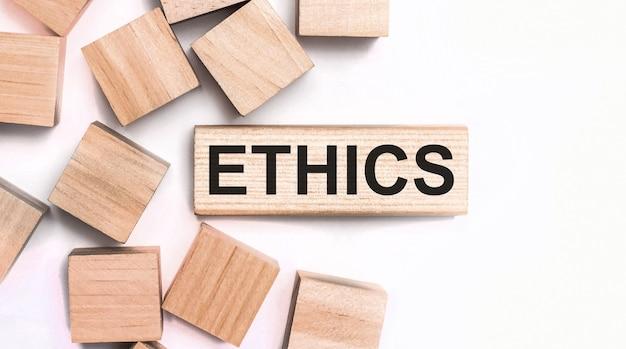 Sobre um fundo claro, cubos de madeira e um bloco de madeira com o texto ética