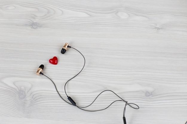 Sobre um fundo claro de madeira, fones de ouvido e um coração vermelho
