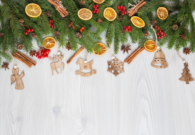 Sobre um fundo claro de madeira, galhos de pinheiro, decoração e brinquedos de madeira feitos à mão