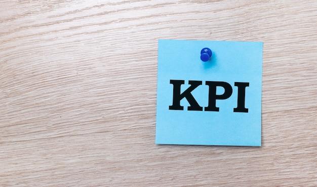 Sobre um fundo claro de madeira, um adesivo quadrado azul claro com o texto kpi.