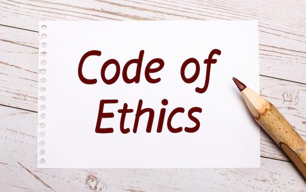 Sobre um fundo claro de madeira, um lápis de cor e uma folha de papel branca com o texto código de ética