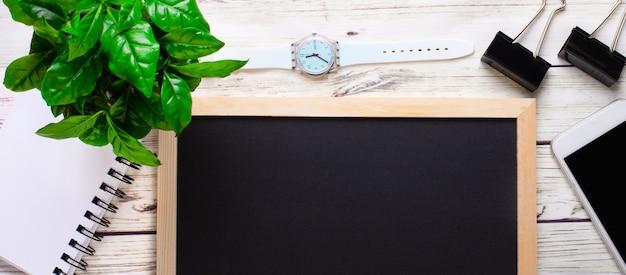 Sobre um fundo claro de madeira, um quadro negro para inscrições, um relógio, um telefone, um caderno. copie o espaço.