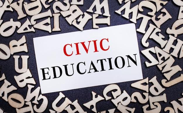Sobre um fundo claro, letras de madeira do alfabeto inglês e um cartão branco dentro com as palavras educação cívica.