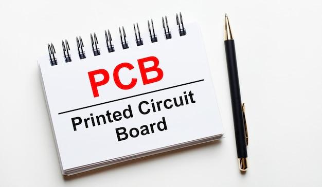 Sobre um fundo claro, um caderno branco com as palavras placa de circuito impresso pcb e uma caneta.