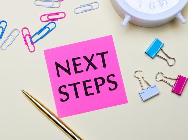 Sobre um fundo claro, um despertador branco, clipes de papel rosa, azul e branco, uma caneta dourada e um adesivo rosa com o texto próximos passos