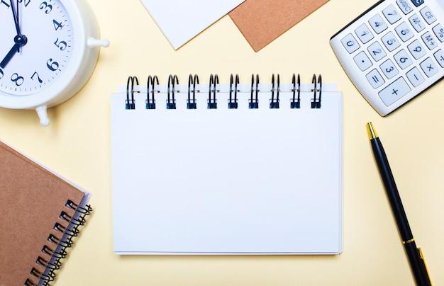 Sobre um fundo claro, um despertador branco, uma calculadora, uma caneta e um caderno com local para inserir textos ou ilustrações. modelo