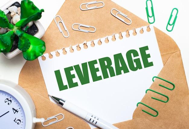 Sobre um fundo claro, um envelope aberto, um despertador branco, uma planta verde, clipes de papel branco e verde, uma caneta branca e uma folha de papel com o texto alavancar