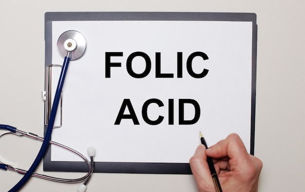 Sobre um fundo claro, um estetoscópio e uma folha de papel, na qual um homem escreve ácido fólico. conceito médico