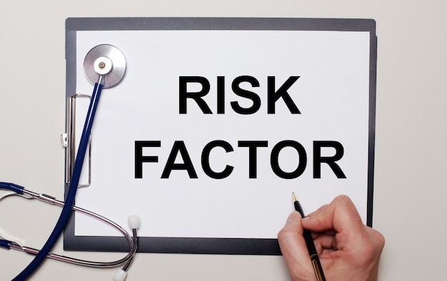 Sobre um fundo claro, um estetoscópio e uma folha de papel, na qual um homem escreve fator de risco
