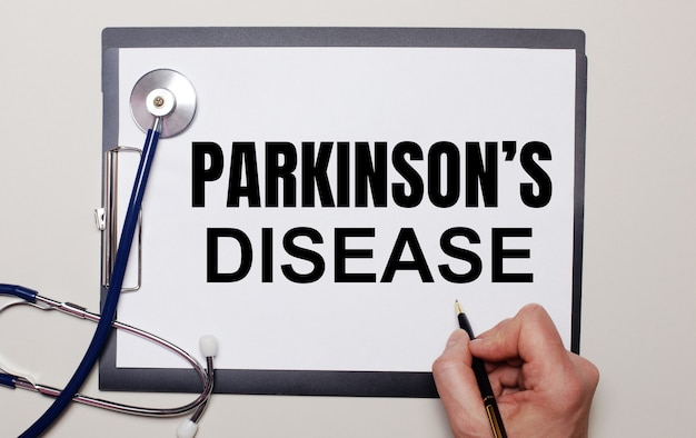 Sobre um fundo claro, um estetoscópio e uma folha de papel, na qual um homem escreve parkinson é doença