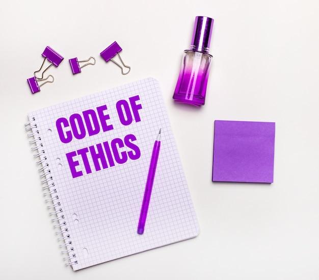 Sobre um fundo claro - um presente lilás, perfume, acessórios de negócios lilás e um caderno com uma inscrição lilás código de ética.
