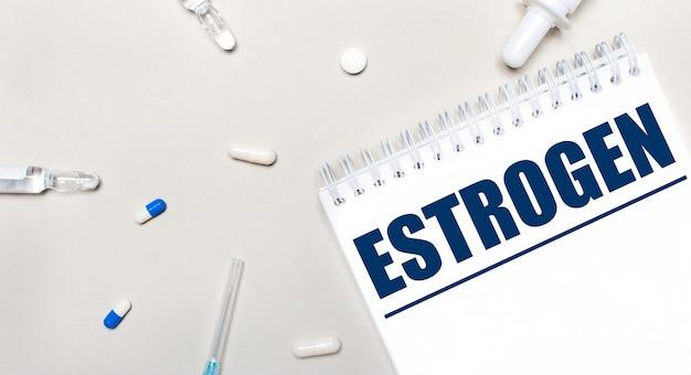 Sobre um fundo claro, uma seringa, um estetoscópio, frascos de remédio, uma ampola e um bloco de notas branco com o texto estrogen. conceito médico