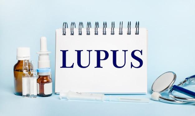 Sobre um fundo claro, uma seringa, um estetoscópio, frascos de remédio, uma ampola e um bloco de notas branco com o texto lúpus. conceito médico