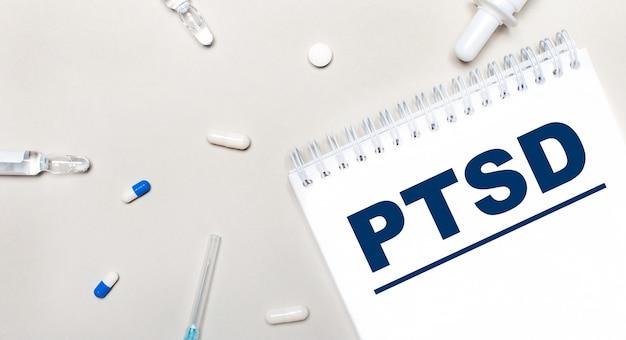 Sobre um fundo claro, uma seringa, um estetoscópio, frascos de remédio, uma ampola e um bloco de notas branco com o texto ptsd. conceito médico