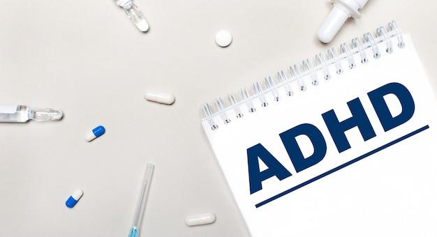 Sobre um fundo claro, uma seringa, um estetoscópio, frascos de remédio, uma ampola e um bloco de notas branco com o texto tdah. conceito médico