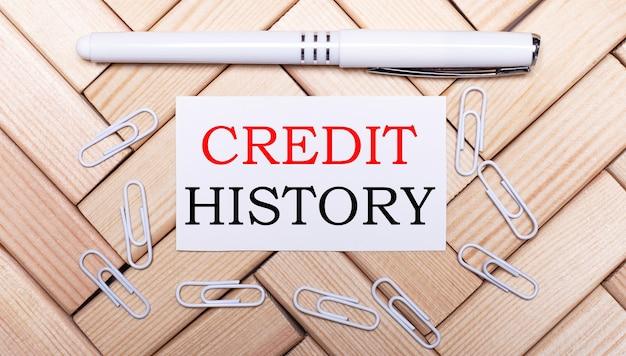 Sobre um fundo de blocos de madeira, uma caneta branca, clipes de papel branco e um cartão branco com o texto história de crédito