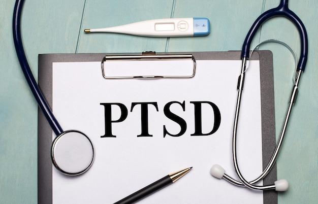 Sobre um fundo de madeira azul claro, há um papel rotulado como ptsd, um estetoscópio, um termômetro eletrônico e uma caneta