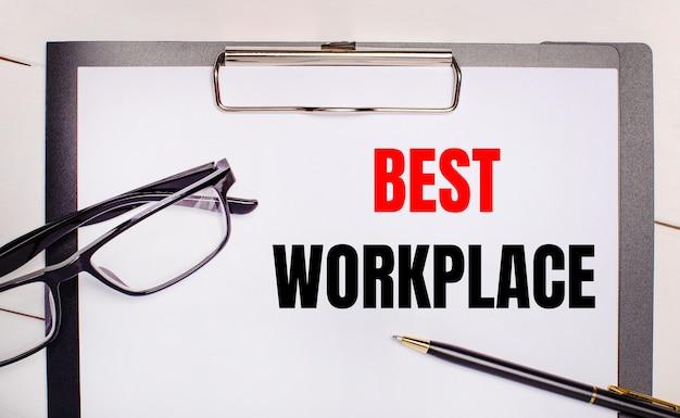 Sobre um fundo de madeira clara, óculos, uma caneta e uma folha de papel com o texto melhor local de trabalho. conceito de negócios