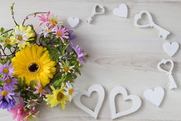 Sobre um fundo de madeira clara, uma coroa de flores, gerberas, corações e chaves