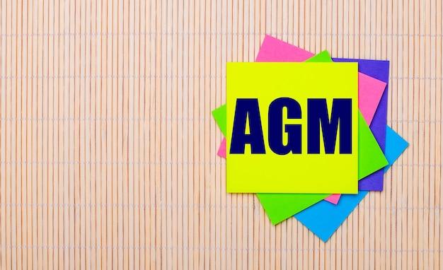 Sobre um fundo de madeira claro, adesivos multicoloridos brilhantes com o texto agm annual general meeting
