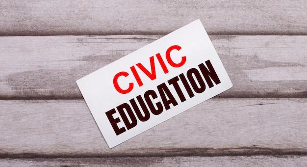 Sobre um fundo de madeira, há um cartão branco com o texto em vermelho educação cívica