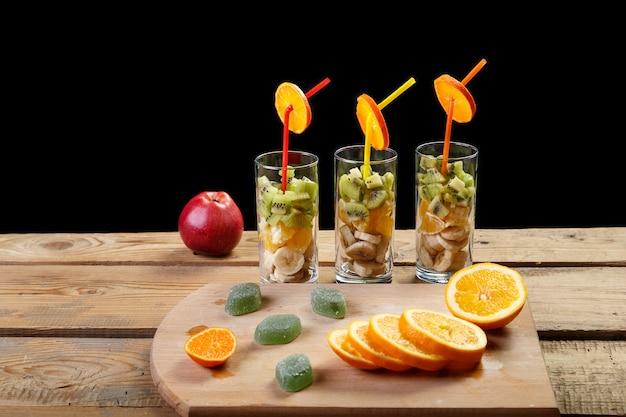 Sobre um fundo de madeira, sobre uma tábua de cortar, estão pedaços de laranja e marmelada ao lado dos copos em que estão pedaços de frui