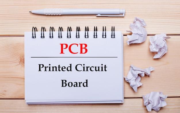 Sobre um fundo de madeira, um caderno branco com a inscrição placa de circuito impresso pcb, uma caneta branca e pedaços de papel branco amassado