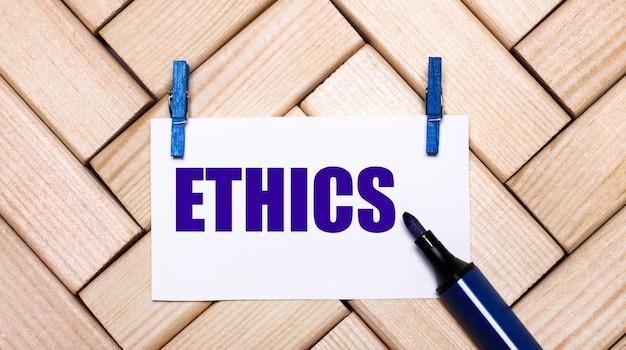 Sobre um fundo de madeira, um cartão branco com o texto ética em prendedores de roupa azuis e um marcador azul. vista de cima