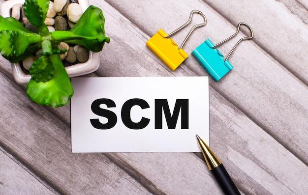 Sobre um fundo de madeira, um cartão branco com o texto scm supply chain management, clipes de papel amarelo e verde e uma planta em um vaso. vista de cima