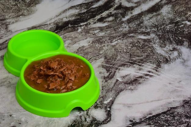 Sobre um fundo de tábuas de madeira cinzentas, encontra-se um prato de plástico verde cheio de comida seca para alimentar cães ou gatos. há um lugar à direita para uma inscrição ou anúncio