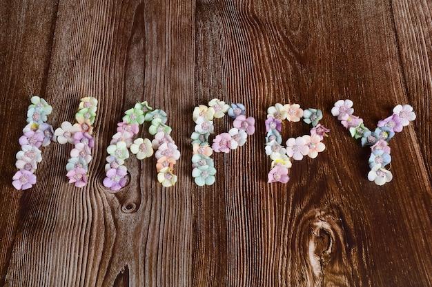 Sobre um fundo escuro de madeira, a palavra feliz está alinhada com flores multicoloridas em letras grandes.