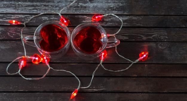 Sobre um fundo escuro de madeira uma xícara de chá sob a forma de um coração com chá vermelho e uma guirlanda