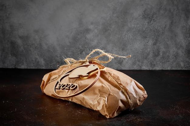 Sobre um fundo escuro de textura, um pacote de presente feito de papel kraft amarrado com barbante com o emblema do ano novo símbolo do mouse feito de madeira compensada