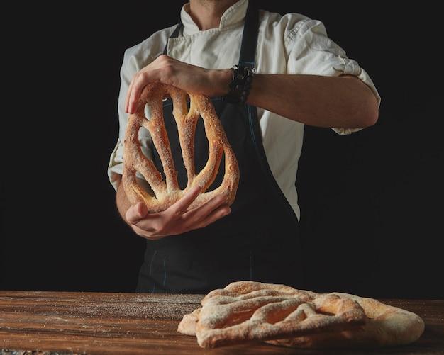 Sobre um fundo escuro e sobre um fundo de uma mesa de madeira marrom, mãos masculinas seguram fougas de pão recém-assado