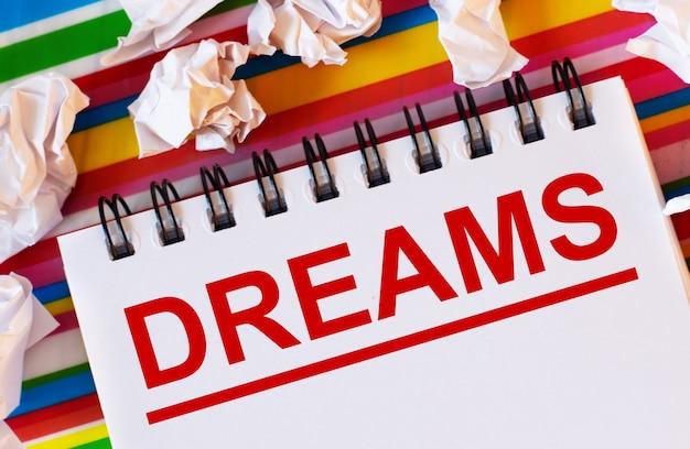 Sobre um fundo listrado multicolorido há pedaços de papel branco e um caderno branco com a inscrição em vermelho sonhos