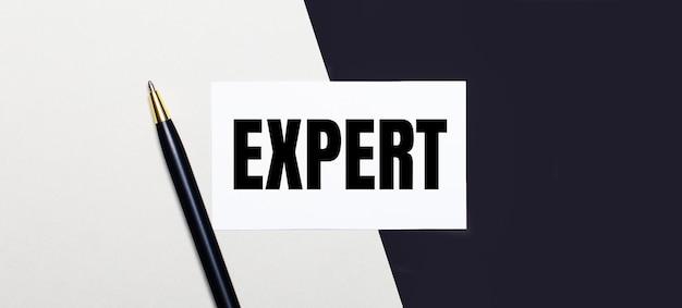 Sobre um fundo preto e branco encontra-se uma caneta e um cartão branco com o texto expert