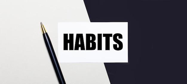 Sobre um fundo preto e branco está uma caneta e um cartão branco com o texto hábitos