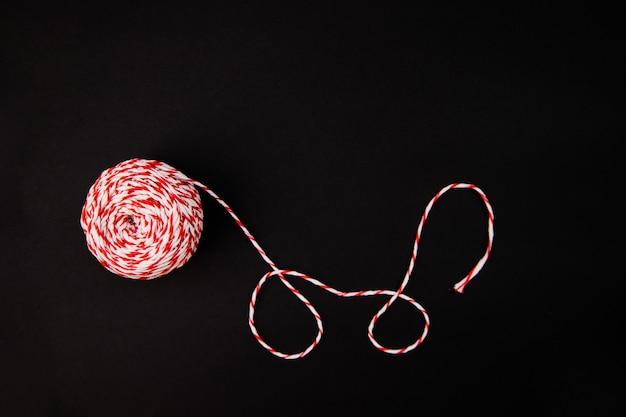 Sobre um fundo preto, uma bola de barbante é vermelha e branca. fios para embrulhar presentes. decoração de natal.