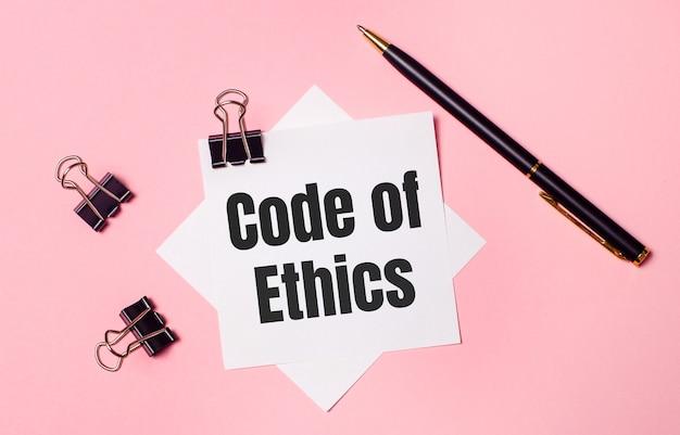 Sobre um fundo rosa claro, clipes de papel pretos, caneta preta e papel branco com as palavras código de ética. postura plana