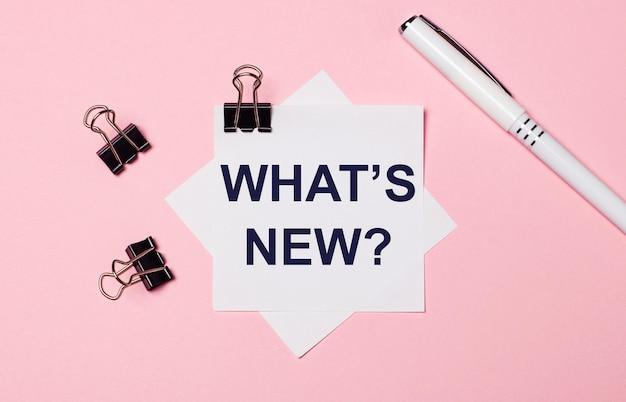 Sobre um fundo rosa claro, clipes de papel pretos, uma caneta branca e um papel branco com o texto o que há de novo. postura plana