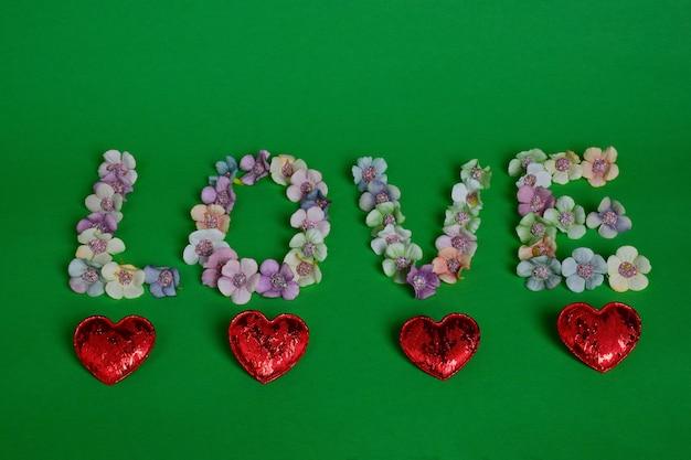 Sobre um fundo verde, a palavra amor está alinhada com letras grandes em flores multicoloridas. corações decorativos alinhados por baixo