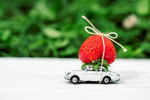 Sobre um fundo verde, um pequeno carro de brinquedo com inscrição de lugar de morangos vermelhos