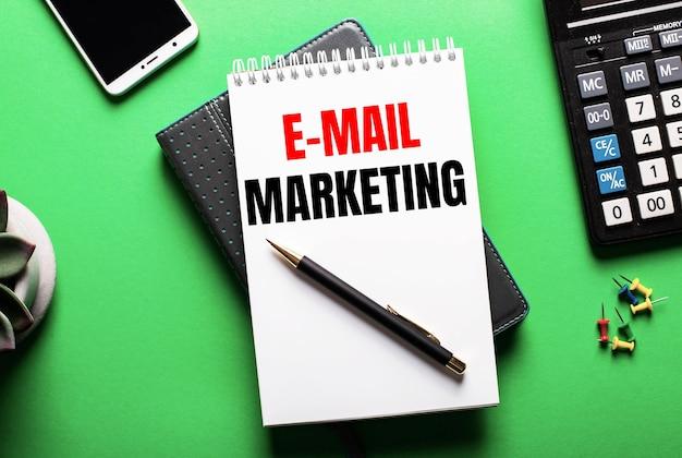 Sobre um fundo verde - um telefone, uma calculadora e um diário com a inscrição e-mail marketing