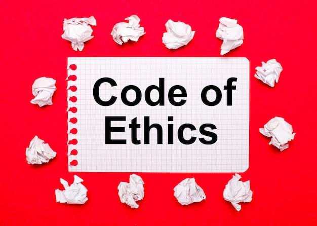 Sobre um fundo vermelho brilhante, folhas de papel branco amassadas e uma folha de papel com o texto código de ética