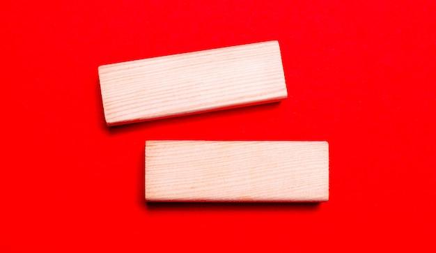 Sobre um fundo vermelho brilhante, há dois blocos de madeira clara com um local para inserir texto.
