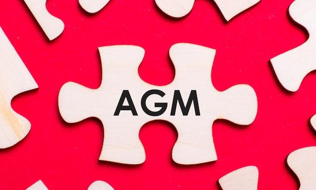 Sobre um fundo vermelho brilhante, quebra-cabeças brancos. em uma das peças do quebra-cabeça, o texto ago assembleia geral anual