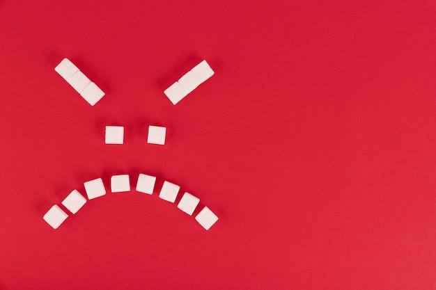 Sobre um fundo vermelho, cubos de açúcar branco, na forma de um emoticon do mal. copie o espaço.
