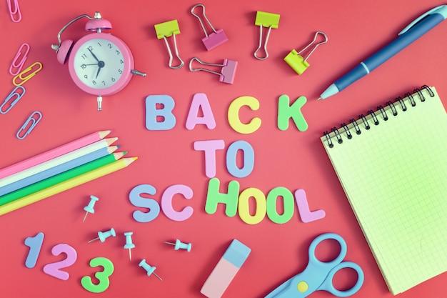 Sobre um fundo vermelho, há clipes de papel, um notebook, um despertador e material escolar.