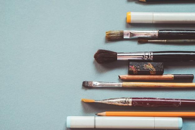 Sobre uma mesa azul estão pincéis e lápis para desenhar