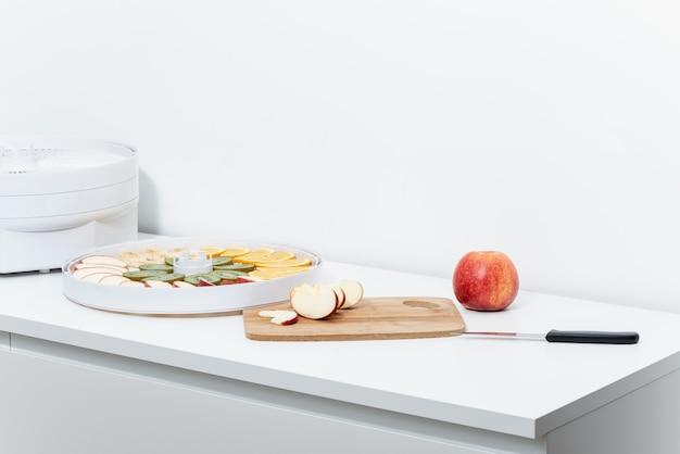 Sobre uma mesa branca há uma maçã vermelha, uma tábua de cortar, uma faca de cozinha, um desidratador e uma bandeja com fatias de frutas.